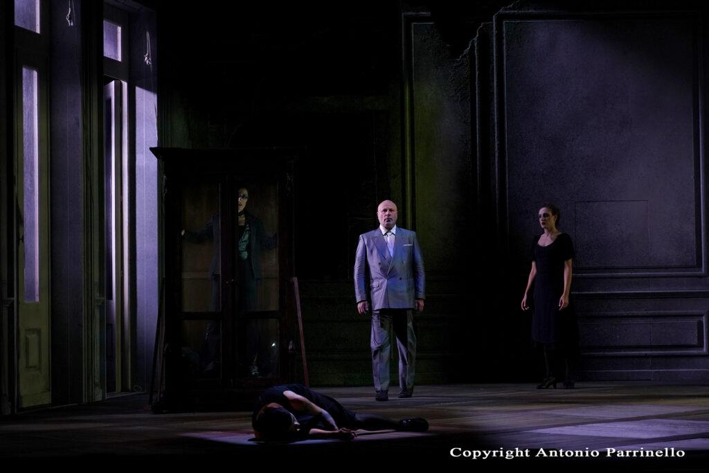 Attori di Baccanti con luce dalla finestra nello spettacolo teatrale del Teatro Stabile